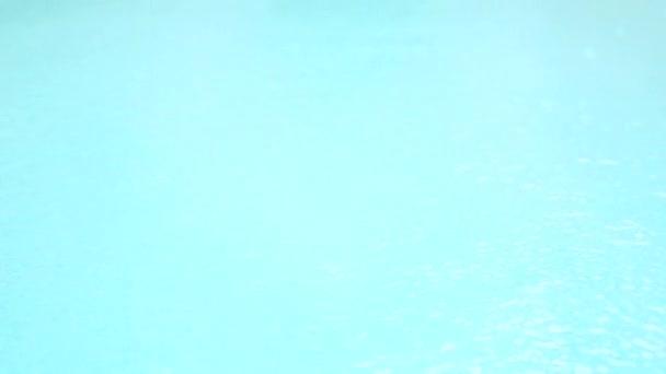Esőcseppek esik a kék víz. Gyönyörű medence víz felszín alatt az eső. Lassú mozgás. 4k