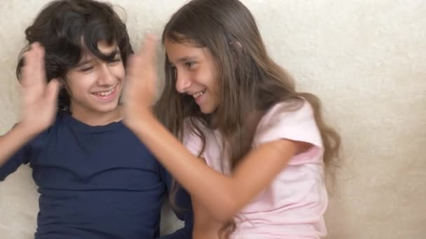 Portrait of adorable brother and sister, teenagers smiling and laughing with funny expression on their faces. Family happiness and relations. 4k, slow motion