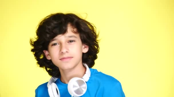 Teenager boy with headphones and mobile phone listening to music on color background. close-up, 4k, slow-motion.