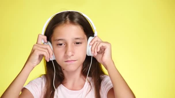 Teenage girl with headphones and mobile phone listening to music on color background. close-up, 4k, slow-motion.