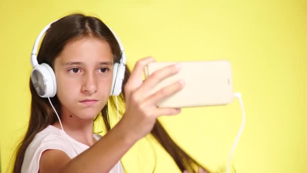 Teenage girl with headphones and mobile phone listening to music on color background. close-up, 4k, slow-motion. makes selfi on smartphone