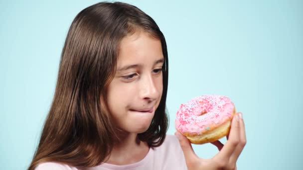 Vértes. portré egy vicces lány hosszú hajat, birtoklás móka-val színes fánk ellen az arcát. Kifejezések, a diéta fogalmát, a háttérszínt