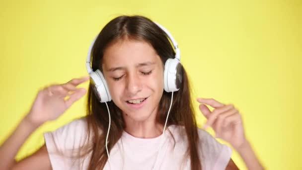 Dospívající dívka s sluchátka poslouchat hudbu na pozadí. detail, 4k, pomalý pohyb.