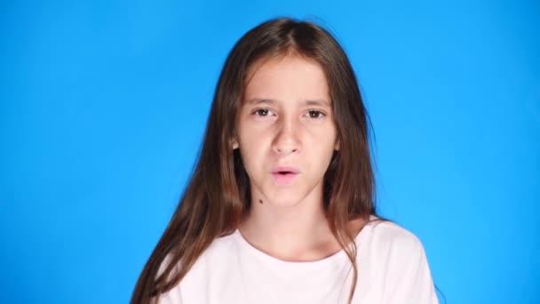 Porträt. Nahaufnahme. ein Teenager-Mädchen auf farbigem Hintergrund. Nahaufnahme, Emotionen der Überraschung. stellt sie eine Frage, was. 4k, Zeitlupe.