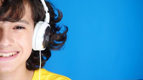 Dospívající chlapec se sluchátky a mobilní telefon poslouchat hudbu na pozadí. detail, 4k, Zpomalený. polovinu tváře