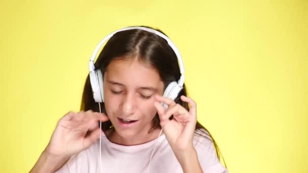Tizenéves lány fejhallgató hallgató-hoz zene, a háttér színét. Közelkép, 4k, lassú mozgás.