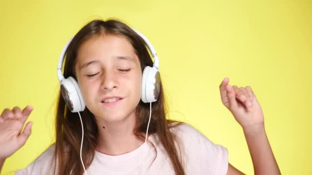 Teenage girl with headphones listening to music on color background. close-up, 4k, slow-motion.