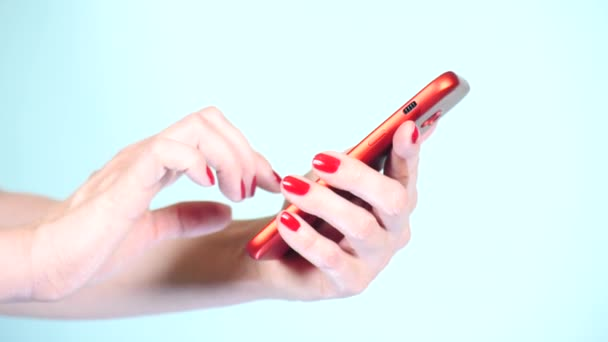 close-up, female hands with red manicure use a smartphone on a colored background. 4k, slow-motion shooting