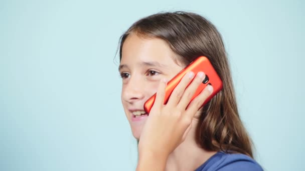 close-up, a teenage girl holding a red smartphone near the ear. the girl is talking on the phone. 4k, slow motion. background color