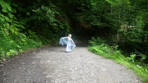 malá holčička model v krásné modré šaty, z lesa po lesní stezce. 4k, pomalý pohyb.