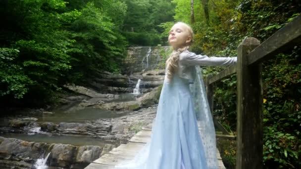 kis lány modell egy gyönyörű kék ruhában pózol egy vízesés, az erdő ellen. 4k, lassú mozgás