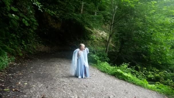 kislány modell egy gyönyörű kék ruha, jön ki az erdőből, egy erdei ösvényen. 4k, lassú mozgás.