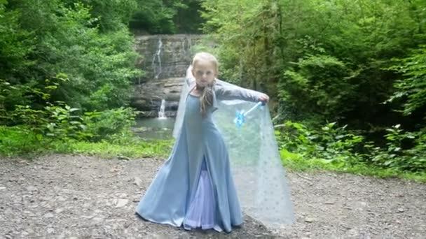malá dívka model v krásné modré šaty, vystupují proti vodopádu v lese. 4k, pomalý pohyb.