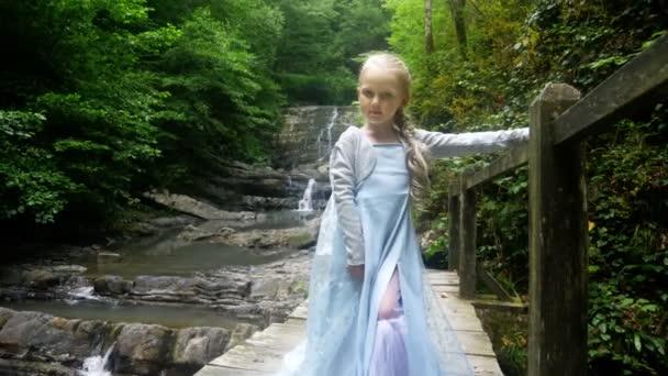 kis lány modell egy gyönyörű kék ruhában pózol egy vízesés, az erdő ellen. 4k, lassú mozgás.