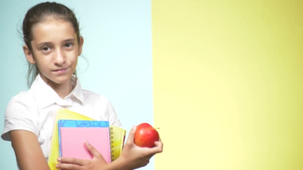 Portraits of a teenage girl in school uniform on a colored background. Funny girl. concept of learning. A teenager is holding books looking at the camera and smiling. copy space
