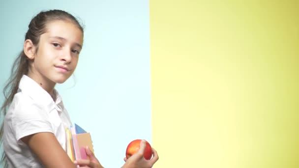 Portréty dospívající dívka ve školní uniformě na barevném pozadí. Funny girl. koncepce výuky. V pubertě je drží knihy, při pohledu na fotoaparát a usmíval se. kopie prostor