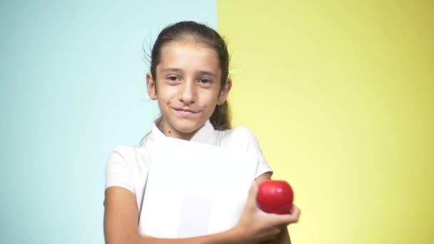 Portréty dospívající dívka ve školní uniformě na barevném pozadí. Funny girl. koncepce výuky. V pubertě je držení notebooku při pohledu na fotoaparát a usmívá se. kopie prostor
