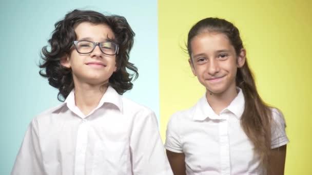 Portréty dětí ve školní uniformě na barevném pozadí. Vtipné děti. Sestra a bratr. koncepce výuky. Dívají se na kameru a úsměv