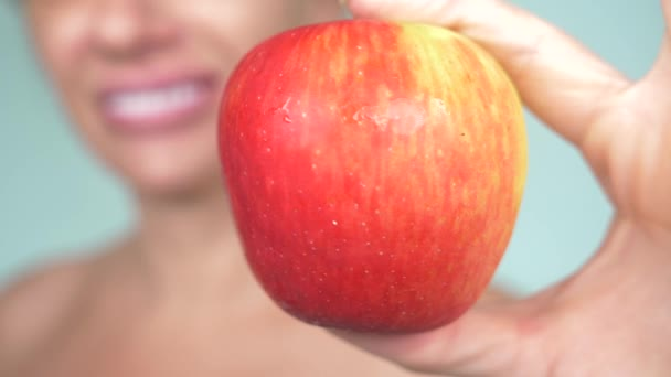 close-up, a girl with a white-tooth smile on a blue background holds a red apple. focus on the apple, blur. 4k, slow motion