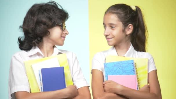 Portréty dětí ve školní uniformě na barevném pozadí. Vtipné děti. Sestra a bratr. koncepce výuky. Oni drží knihy, při pohledu na fotoaparát a usmíval se. kopie prostor