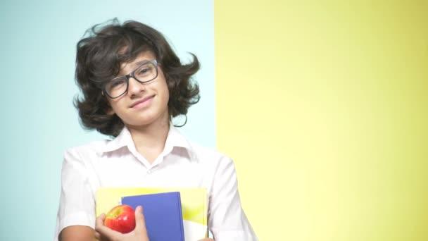 Portréty dospívající chlapec ve školní uniformě na barevném pozadí. Vtipálek. koncepce výuky. V pubertě je drží knihy, při pohledu na fotoaparát a usmíval se. kopie prostor