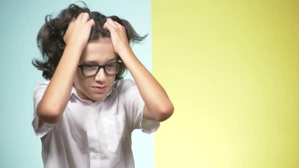 Portréty v pubertě ve školní uniformě a brýle na barevném pozadí. koncepce výuky. Teenager dělá legrační obličeje. zoufal on, protože on nechce jít do školy. kopie prostor