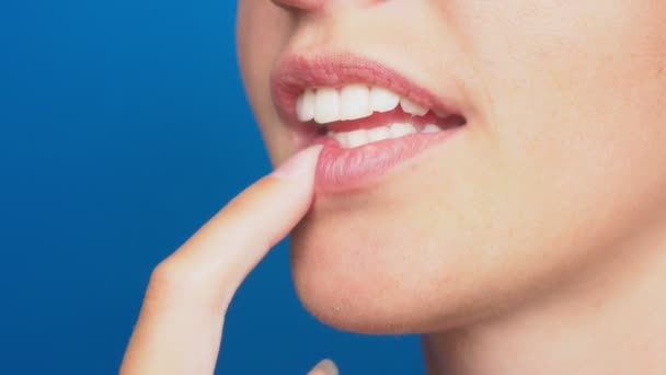 closeup, female lips without makeup, girl chewing nails, on a blue background. 4k, slow motion
