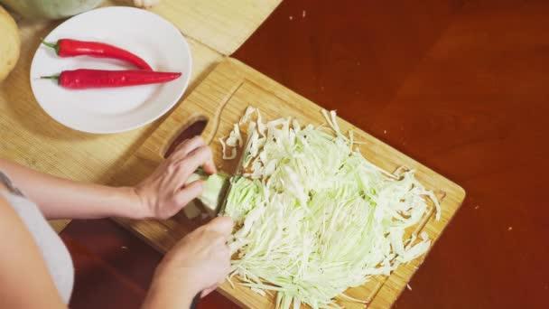 női kezek vágott káposzta, egy késsel. zöldségek, zöldség pörkölt főző keveréke. Nézd meg felülről. 4k, az egészséges táplálkozás és betakarítás.