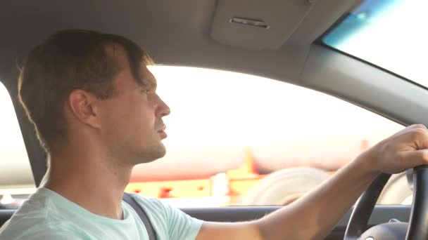 muž za volantem auta, jí rychlého občerstvení, zatímco auto je v pohybu. v letní slunečný den. 4k, pomalý pohyb
