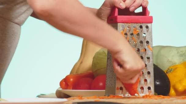 ženské ruce třel na strouhané mrkve. směs zeleniny vaření dušené zeleniny. Barva pozadí. 4k, koncept zdravého stravování a sklizně