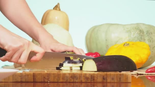 ženské ruce uřezal lilek s nožem. směs zeleniny vaření dušené zeleniny. Barva pozadí. 4k, koncept zdravého stravování a sklizně.