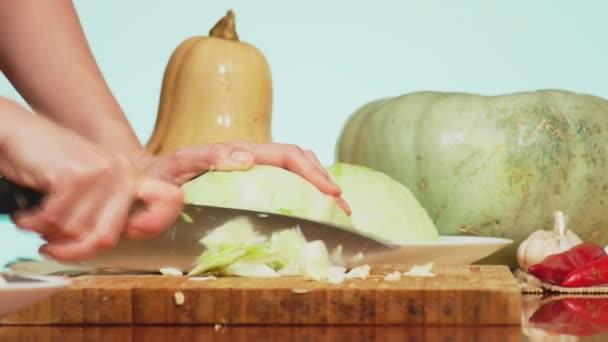 ženské ruce zelí s nožem. směs zeleniny vaření dušené zeleniny. Barva pozadí. 4k, koncept zdravého stravování a sklizně.
