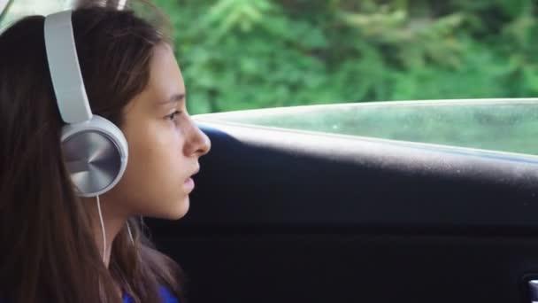 Malá elegantní dívka v klobouku a sluneční brýle poslechu hudby ve sluchátkách od jejího smartphone, ona jezdí v autě na zadním sedadle. 4k, pomalý pohyb