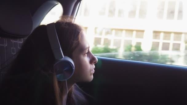Ein kleines stylisches Mädchen mit Hut und Sonnenbrille, das über Kopfhörer von seinem Smartphone Musik hört, fährt im Auto auf dem Rücksitz. 4k, Zeitlupe