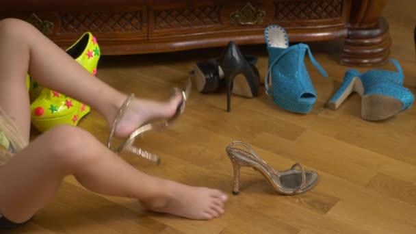 Ein kleines Mädchen spielt mit Stöckelschuhen. die Beine eines kleinen Kindes in Schuhen für Erwachsene. Mädchen in High Heels. 4k, Nahaufnahme