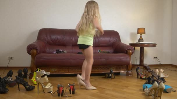 A little girl is playing with high-heeled shoes. The legs of a small child in shoes for adults. girl in high heels. 4k