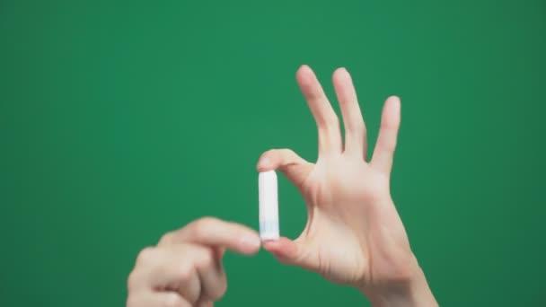 detail, ženské ruce držte tampon na zeleném pozadí. 4k, pomalý pohyb