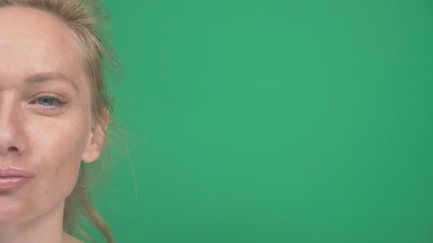 niedliche junge blonde Frau. auf grünem Hintergrund. zeigt Emotionen. sie prüft etwas. Schwerpunktwechsel. Zeitlupe, Nahaufnahme, halbes Gesicht