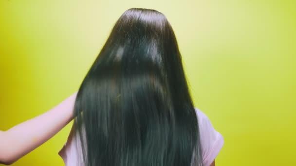 das Konzept des Haarfärbens, Tonisierens, Haarfärbens. das Mädchen auf gelbem Grund, zeigt fröhlich ihre langen, blau geschminkten Haare. 4k, Zeitlupe.