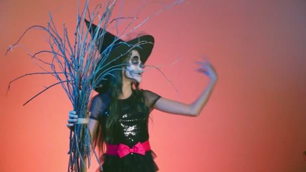 Halloween dívka s make-up kostra na polovinu tváří, oblečený jako čarodějnice, pózování a tančí na červeném pozadí. 4k, pomalý pohyb