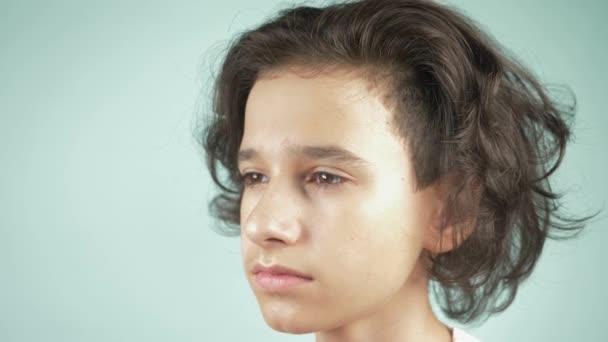 Ten chlapec drží čelo rukou. Dospívající chlapec s příznaky bolesti hlavy, migrain nebo stresu. 4 k, Zpomalený, detail