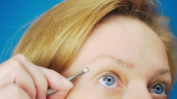 Extrémní detail. škubání obočí pinzetou, Blondýnka s modrýma očima vytáhne zbytečné chlupy z její obočí, pomalý pohyb