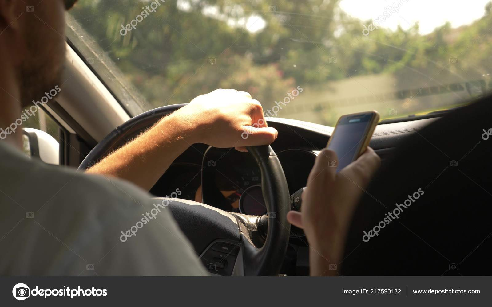 Ein schöner junger Mann mit Sonnenbrille ist ein Auto durch
