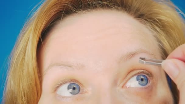 Extreme close-up. plucking eyebrows tweezers, a blonde girl with blue eyes pulls out unnecessary hairs from her eyebrow, slow motion.