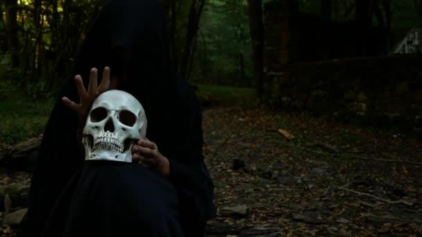 Hrozně zlá čarodějnice v podzimním lese drží lidská lebka, seděl na kládě.