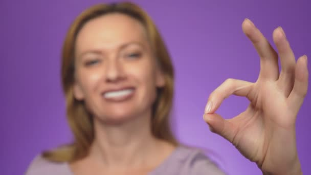 Happy young woman showing ok sign with fingers and winking. background color