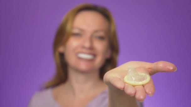 Young beautiful woman, blurred in the background, smiling. in focus is her hand holding an open condom, the concept of safe sex. Protection against AIDS and birth control, color background