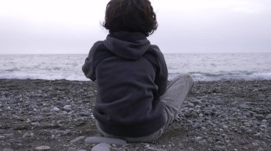 A lonely boy sits on the shore and throws stones at sea.