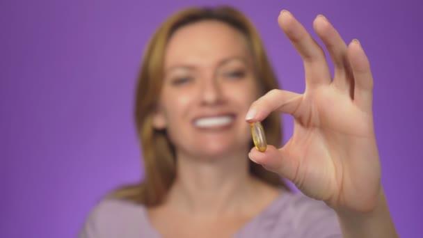 Zdravé dietní jídlo. Krásná usměvavá mladá žena držící rybí olej pilulku v ruce. Closeup. užívání kapslí. Vitamínů a potravinových doplňků. Barva pozadí, rozostření, 4k