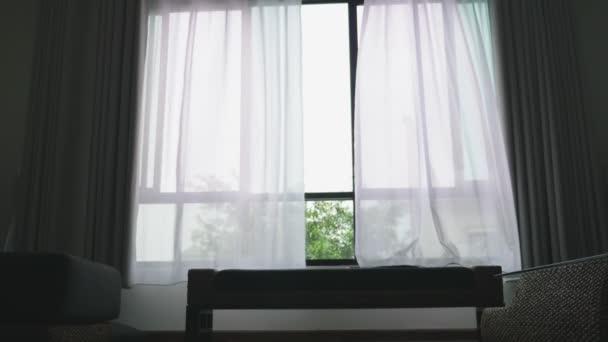 Průhledné okno závěs, jemně posune větrem. za oknem můžete vidět že zelené listí stromů